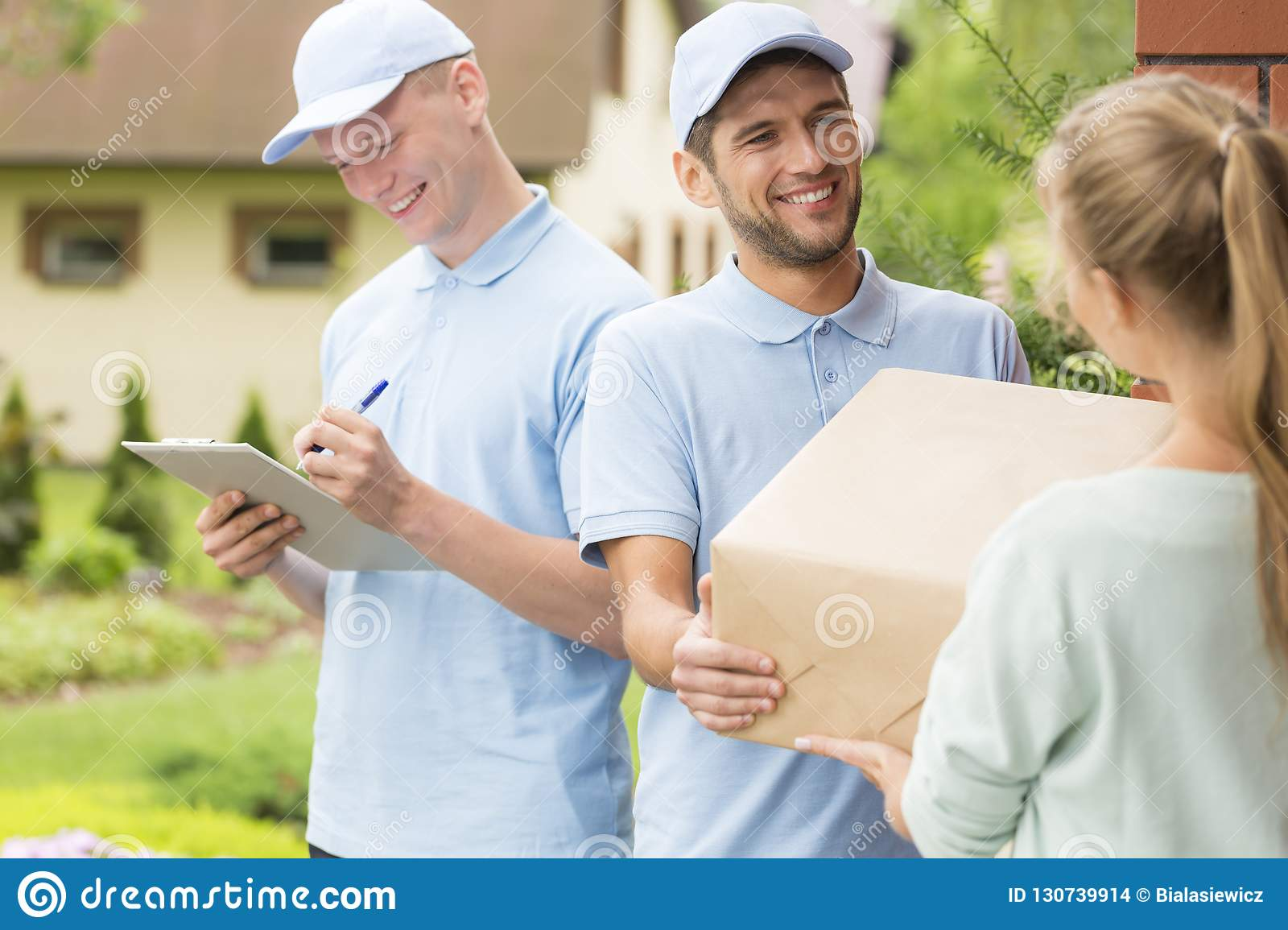 Couriers in blue uniforms and caps giving package to a customer