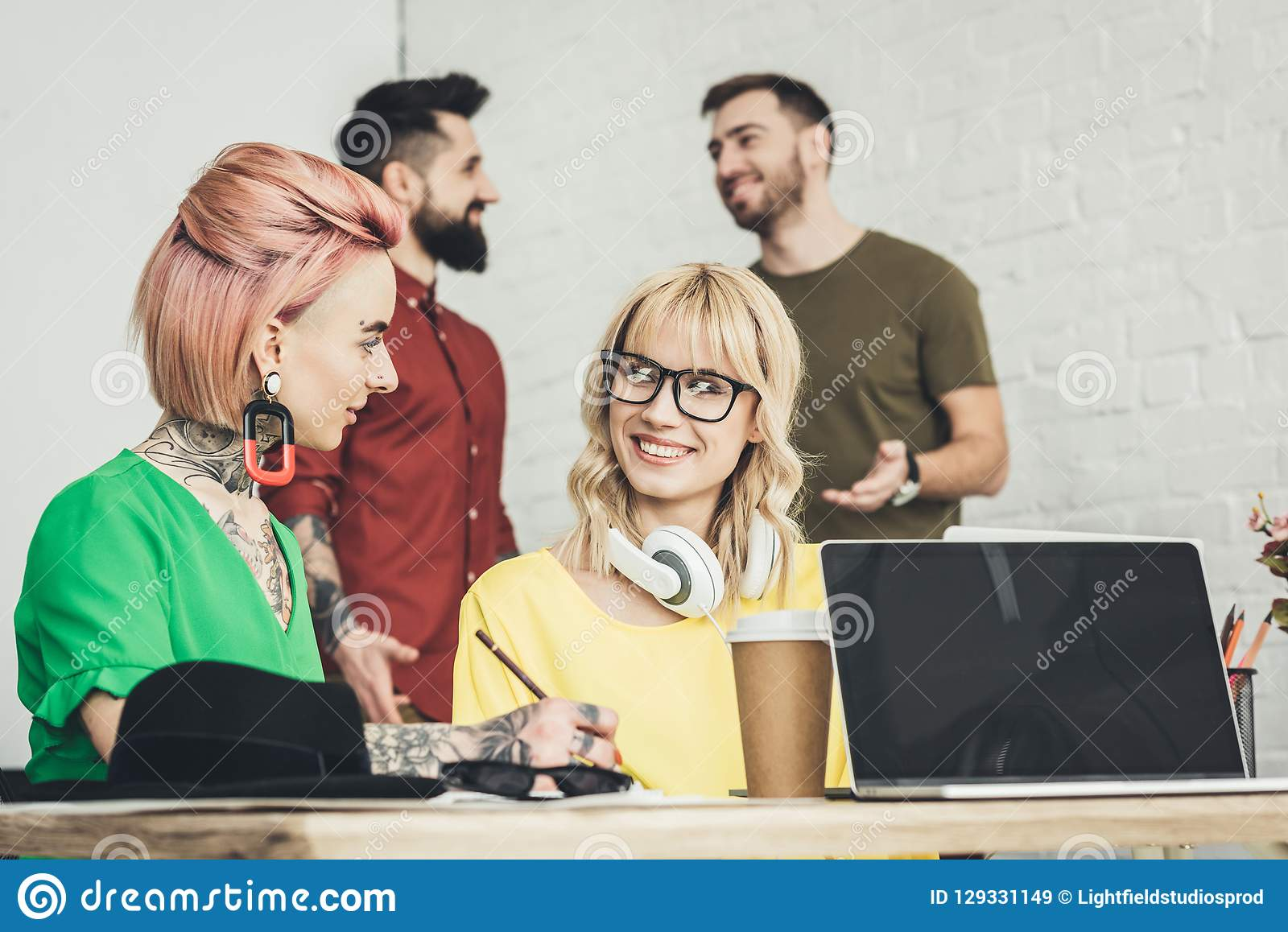 Smiling creative businesswomen working on project together while colleagues talking behind in office royalty free stock images
