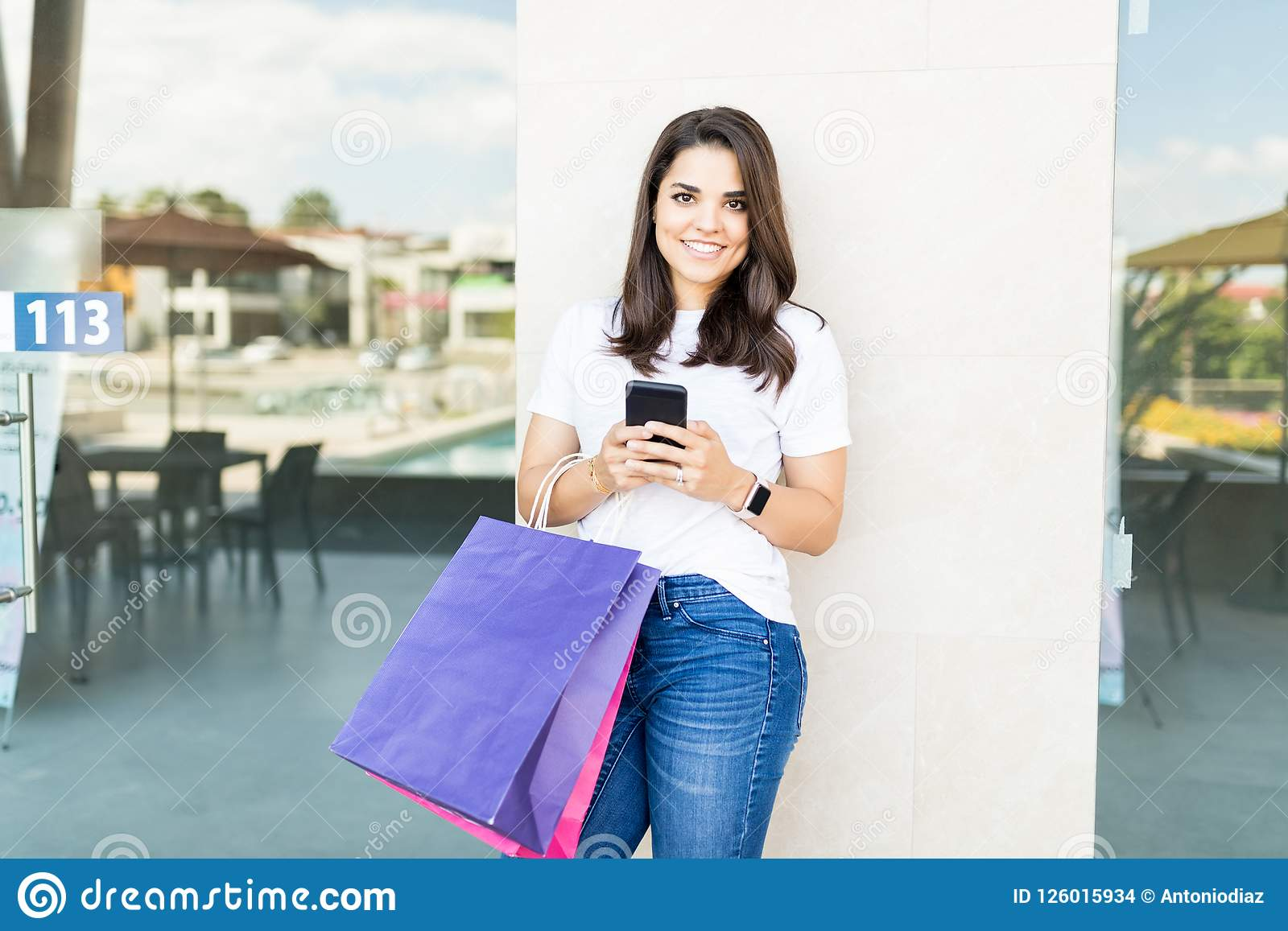 Smiling Customer With Shopping Bags Using Mobile Phone In Mall