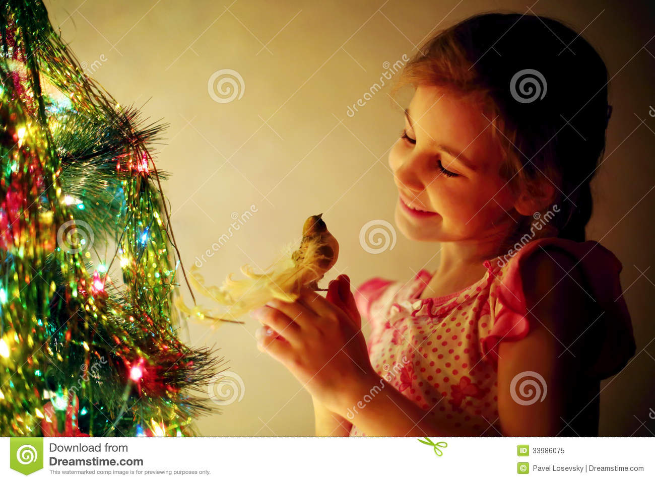 Smiling cute girl holds toy bird next to Christmas tree