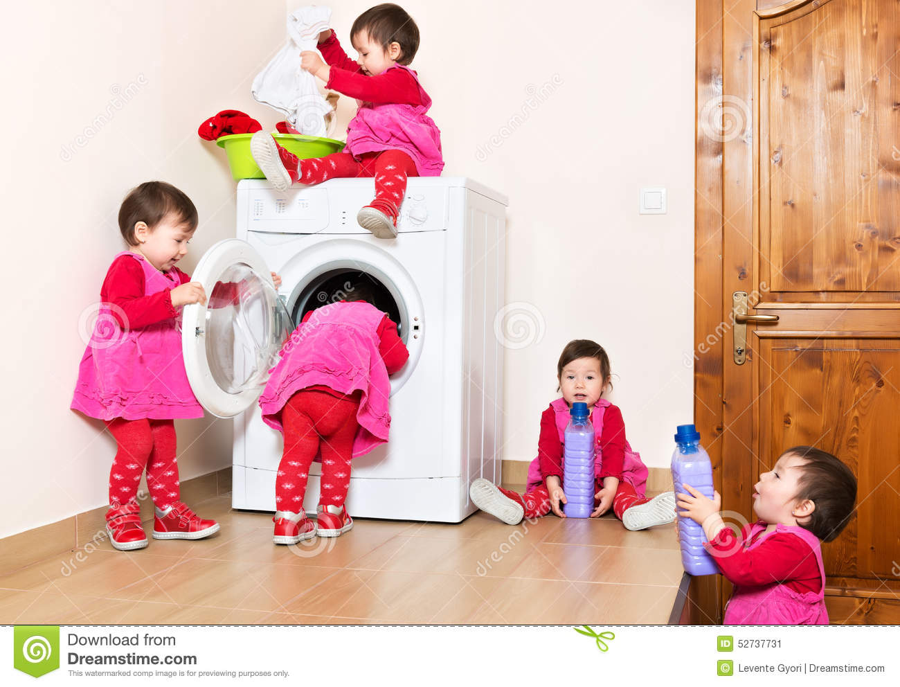 Smiling cute little child using washing machine at home for Aide a la maison
