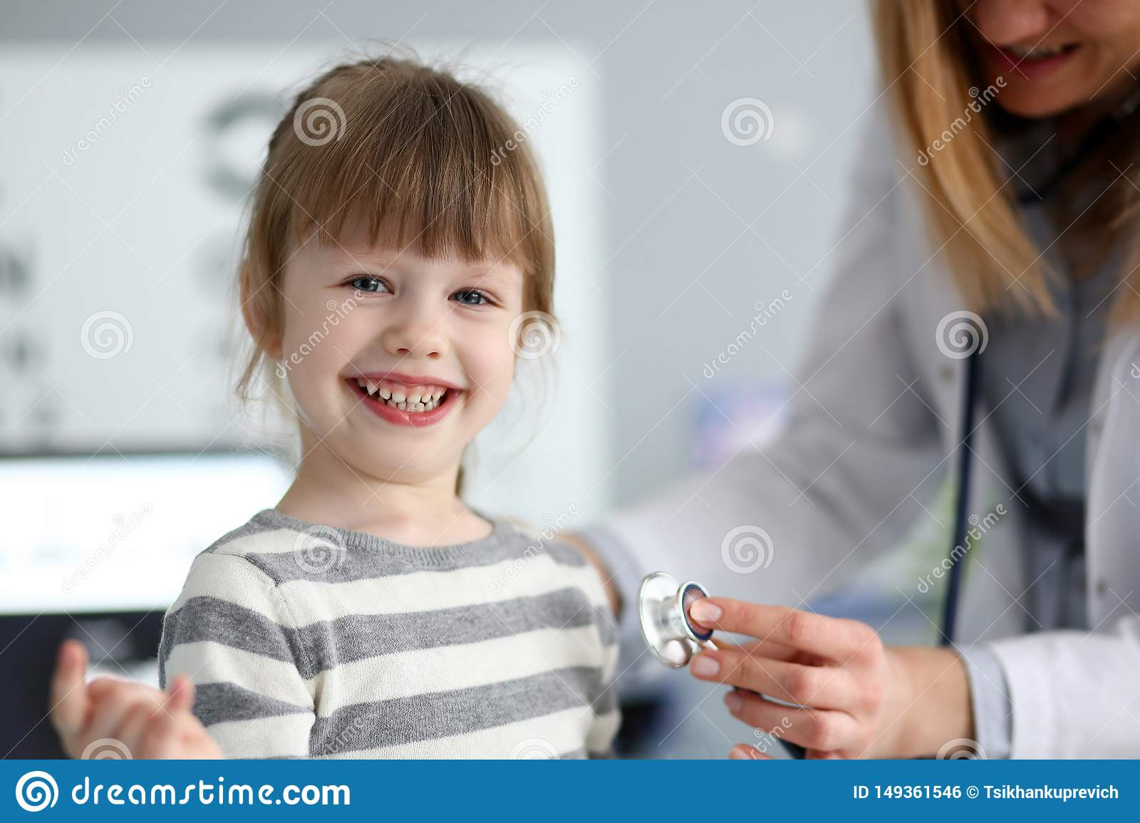 Smiling cute little girl with doctor measuring heart beat with stethoscope