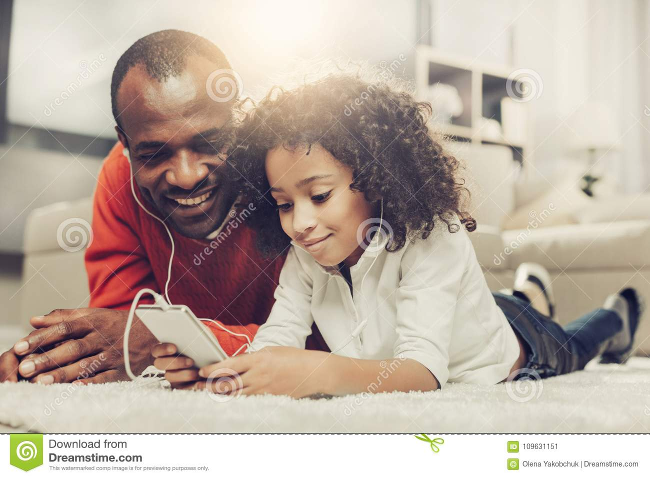 Glad father and kid using mobile phone with earpieces