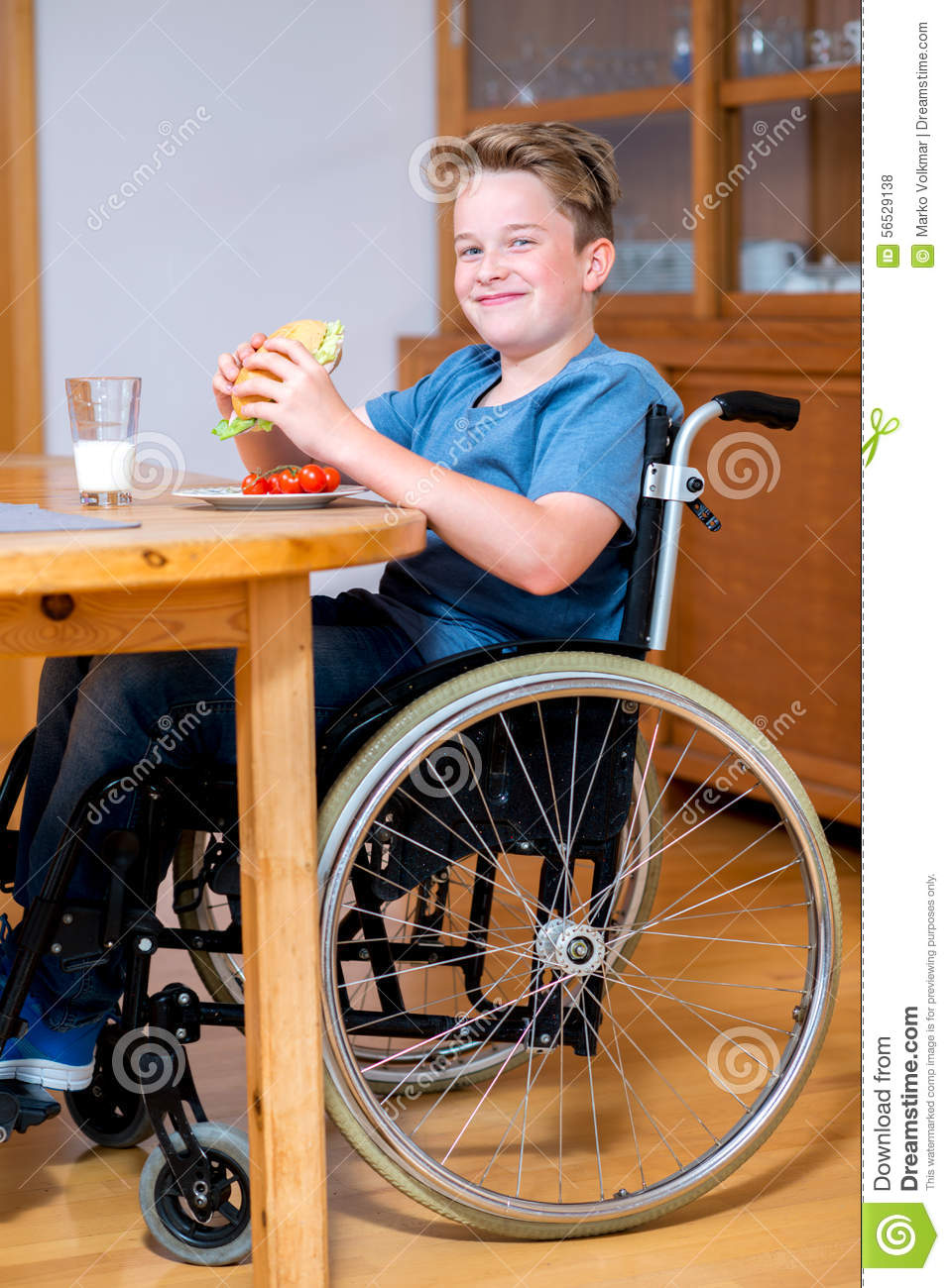 Smiling Disabled Boy In Wheelchair Is Eating Stock Photo