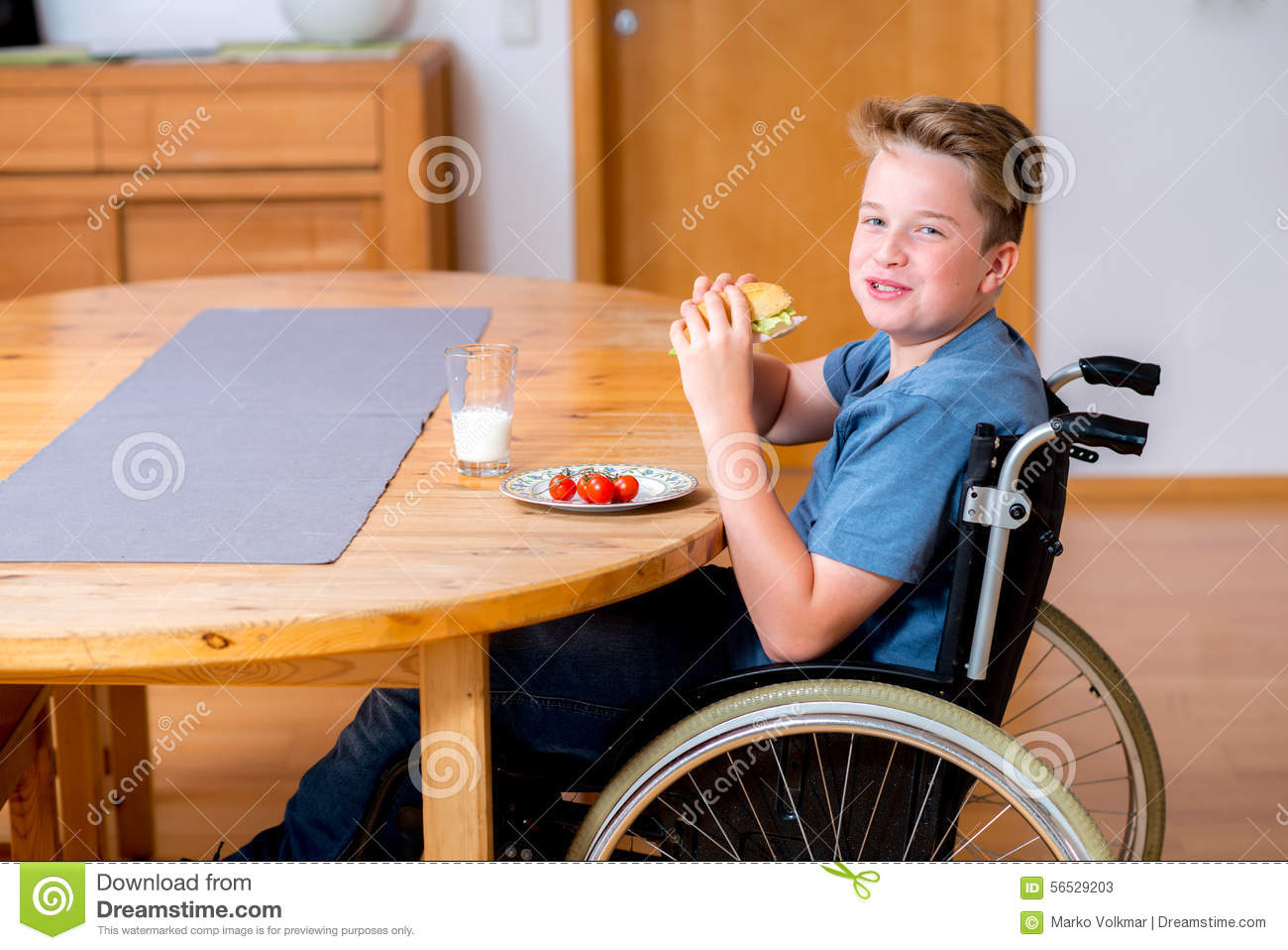 Smiling Disabled Boy In Wheelchair Is Eating Stock Image