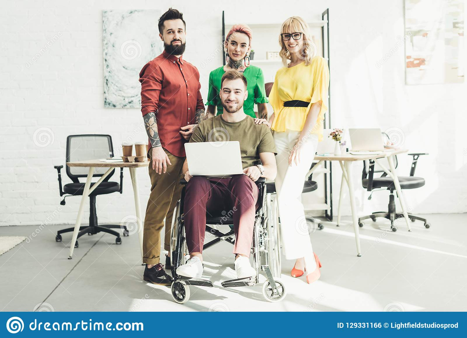 Smiling disabled businessman with laptop and colleagues standing behind in office royalty free stock image