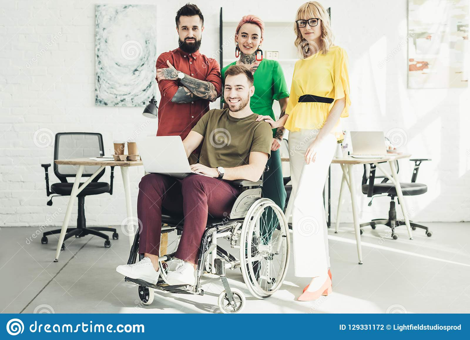 Smiling disabled businessman with laptop and colleagues standing behind in office stock photography