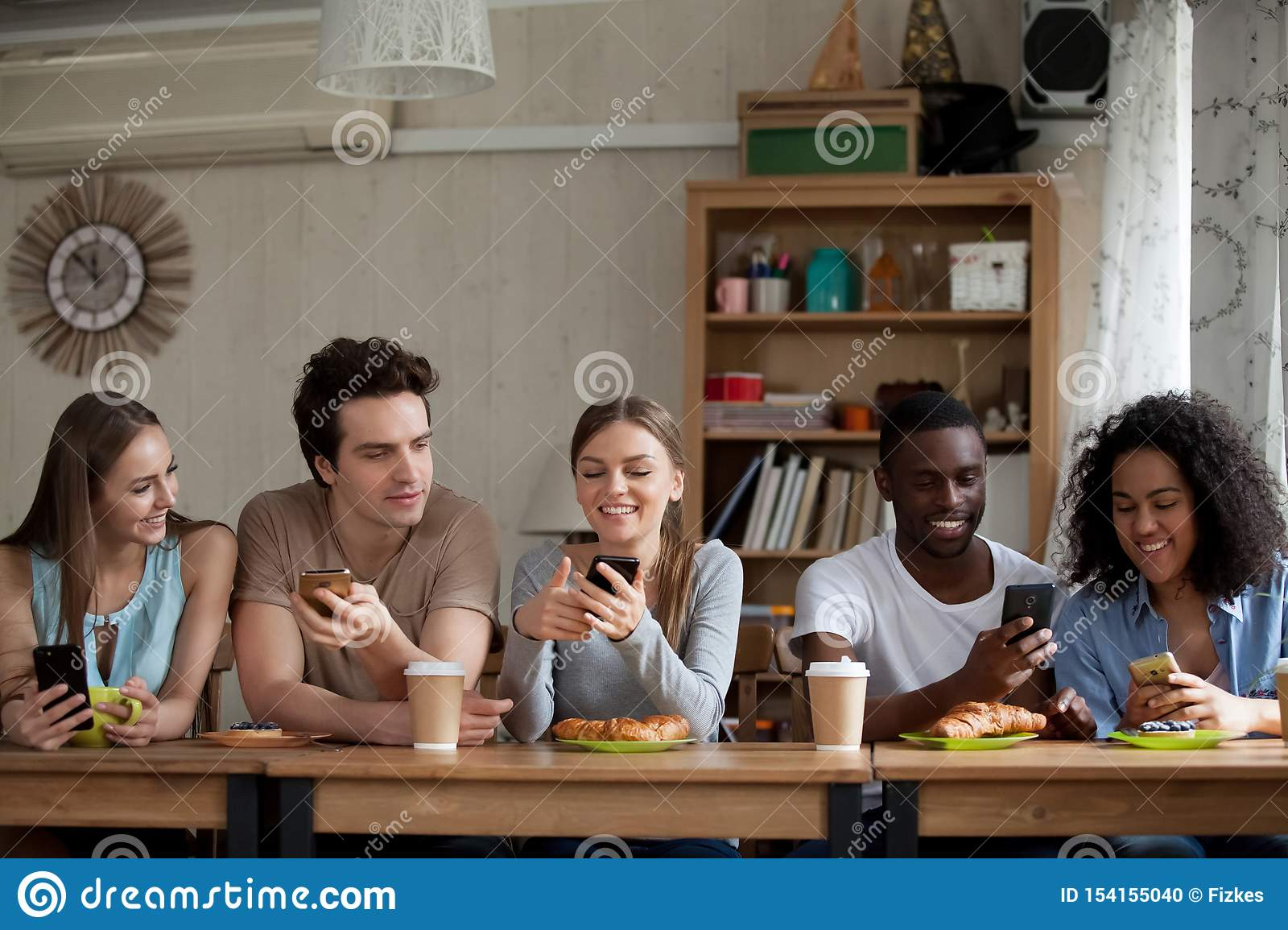 Smiling diverse young women and men using smartphones in cafe.