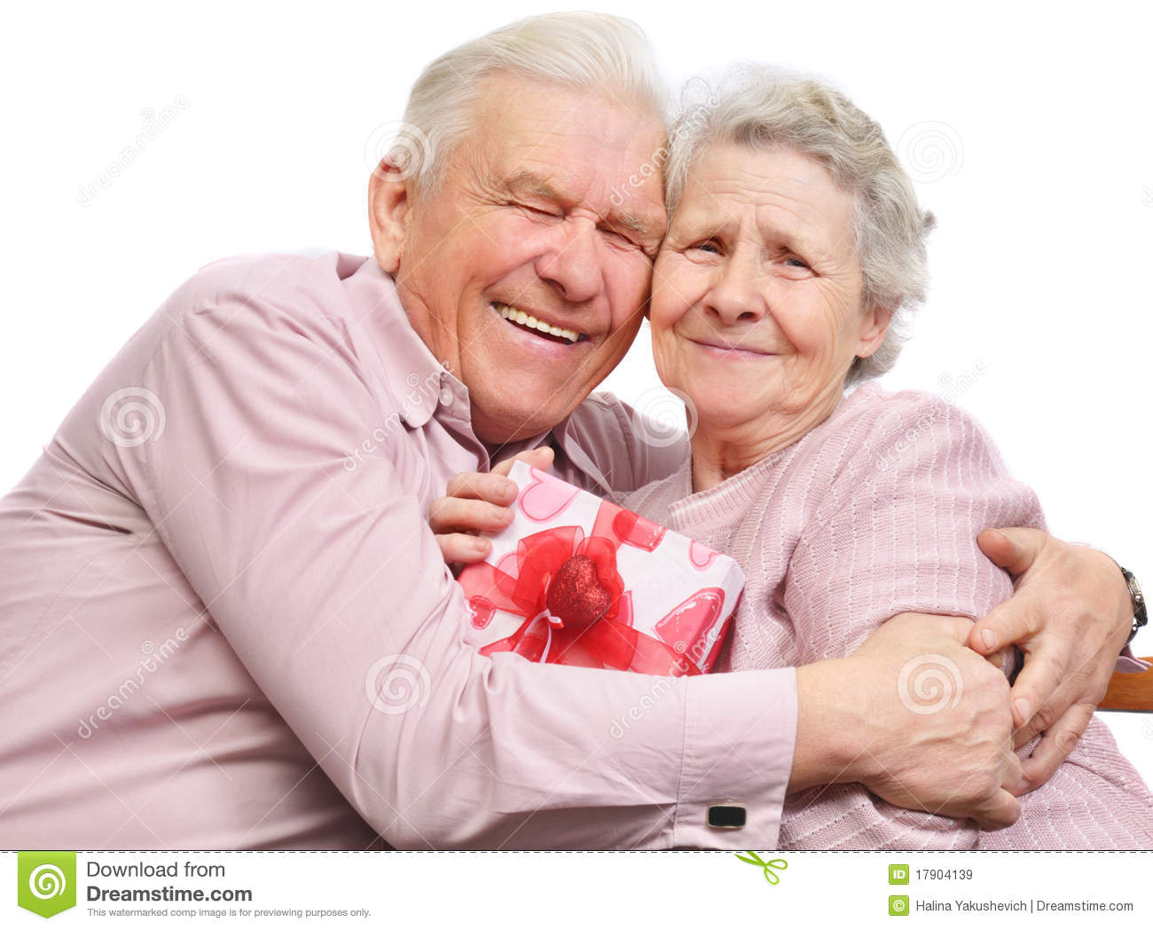 Smiling Elderly Couple And Box With Gift Royalty Free