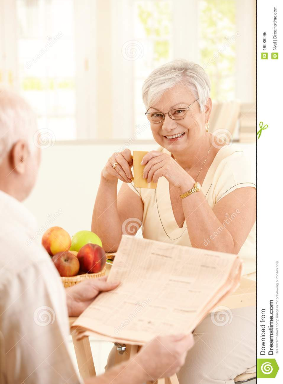 elderly wife chatting to husband at breakfast stock