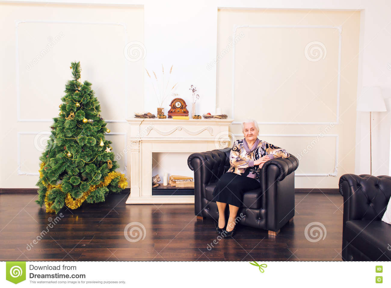 Smiling elderly woman relaxing in front of a decorated Christmas tree in her living room