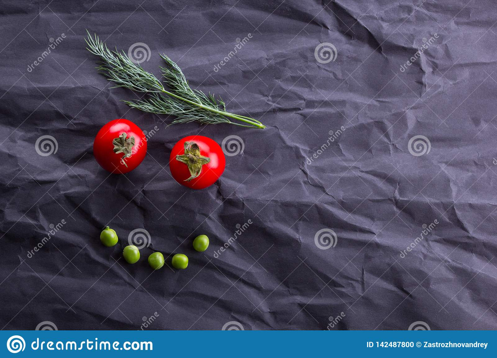 Smiling face from vegetables on black paper background