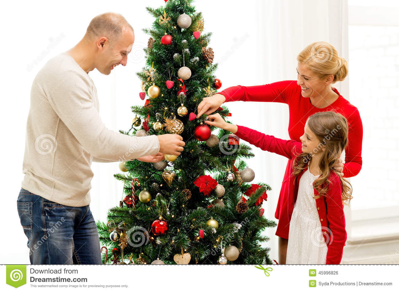 People Decorating smiling family decorating christmas tree at home stock photo