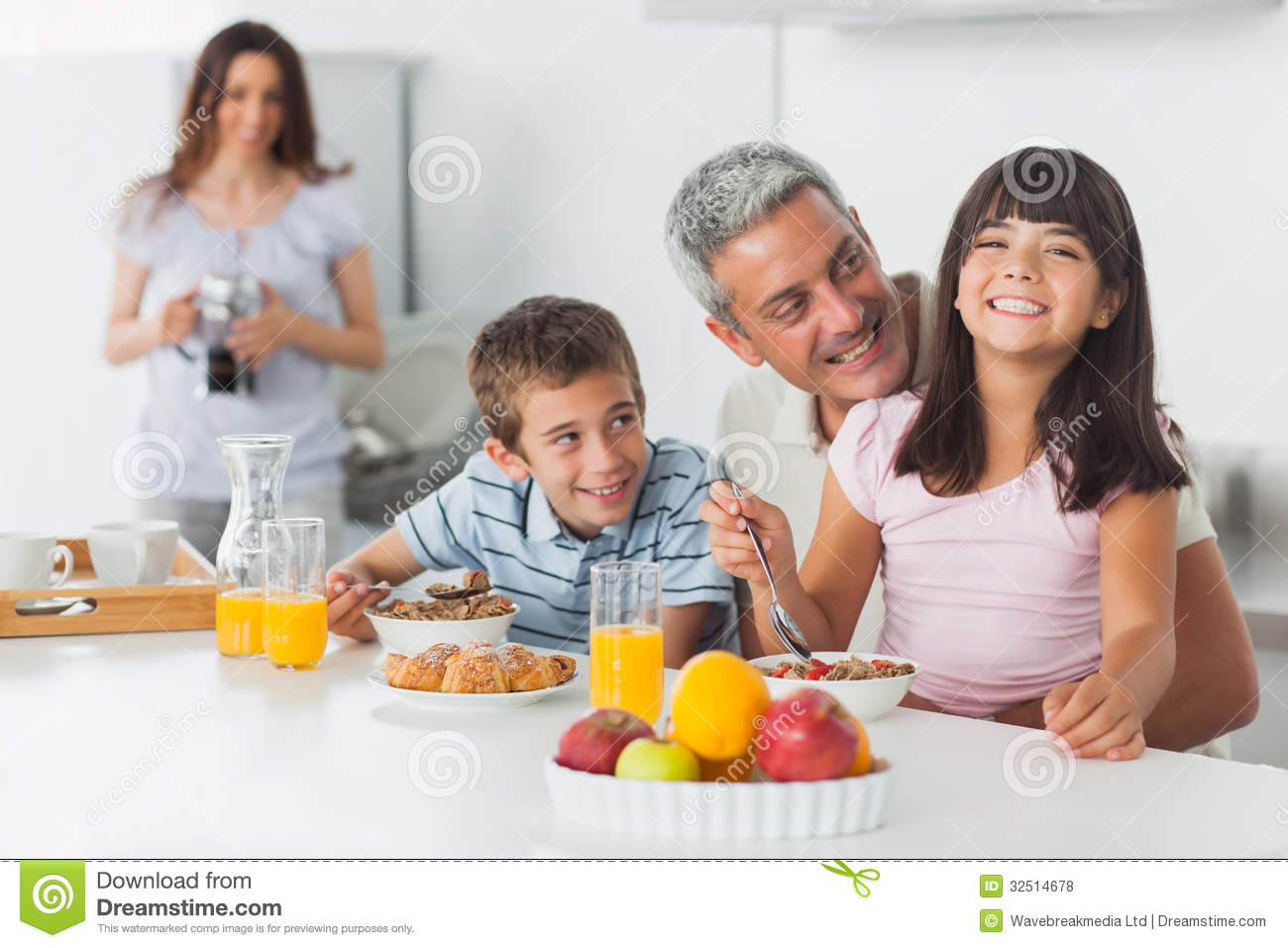 Smiling Family Eating Breakfast In Kitchen Together ...