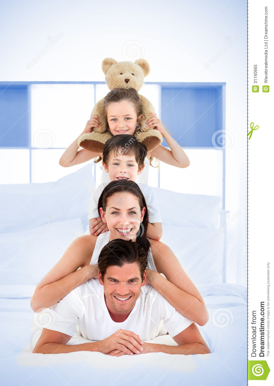Smiling Family Leaning On Each Others Shoulders In Bed ...