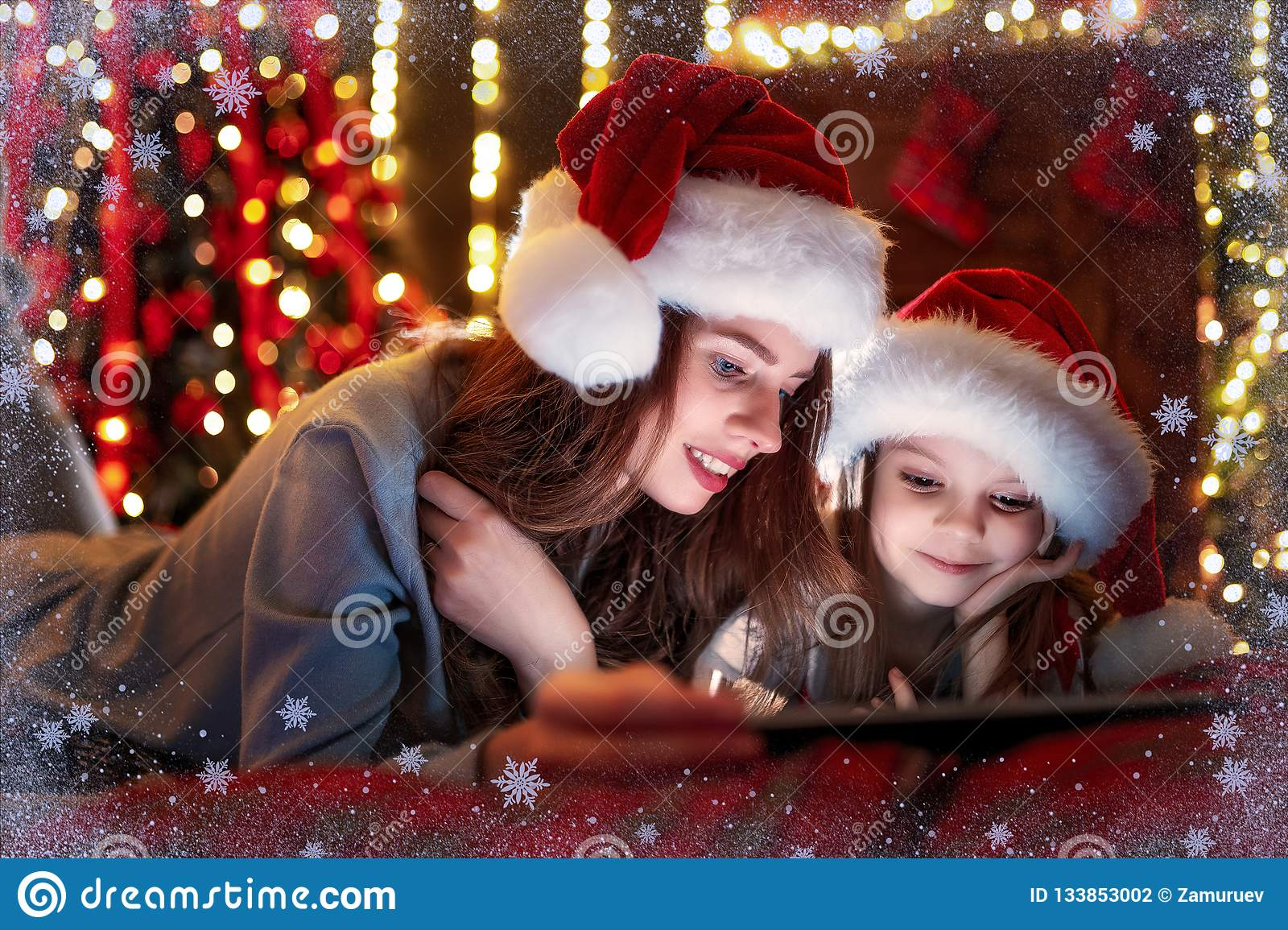 Smiling family mother and daughter in santas hats and pajamas watching funny video or choosing gifts on digital tablet