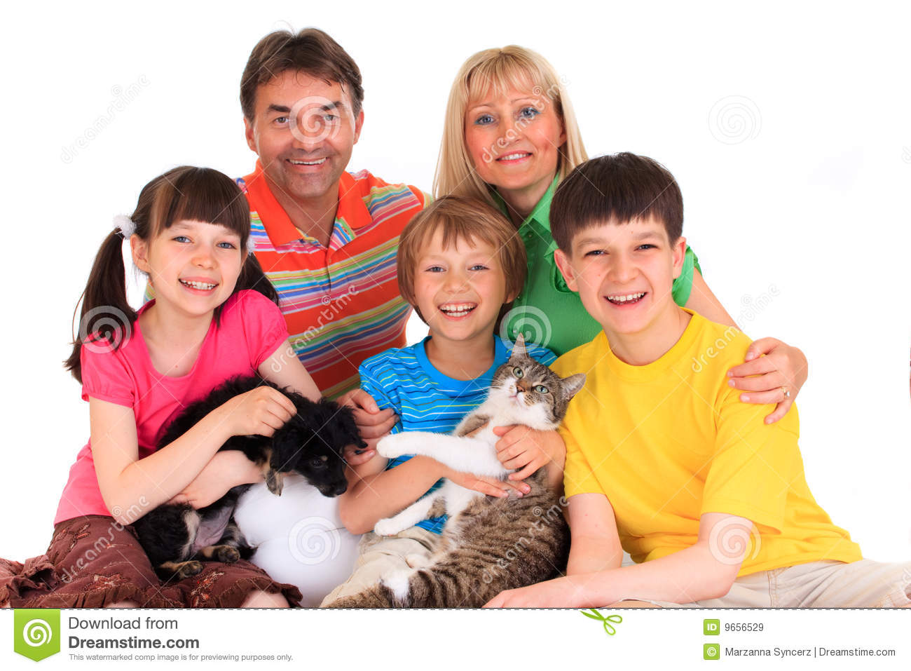 ... view of a smiling family posing with their pets on a white background