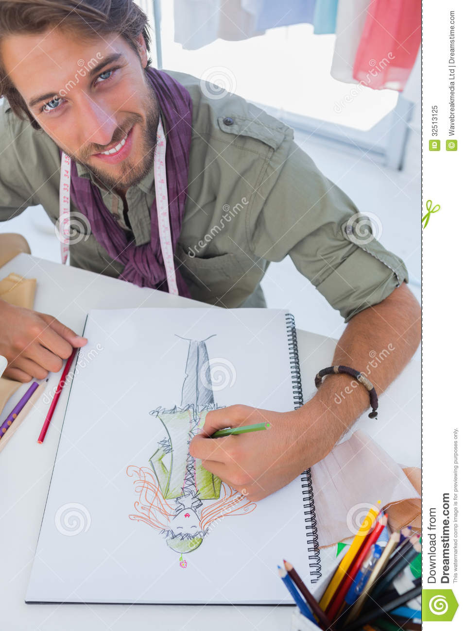 Smiling Fashion Designer Drawing A Coat Royalty Free Stock