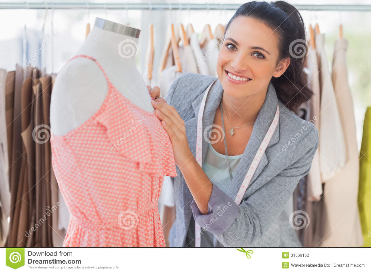Smiling Fashion Designer Fixing Dress On A Mannequin Stock