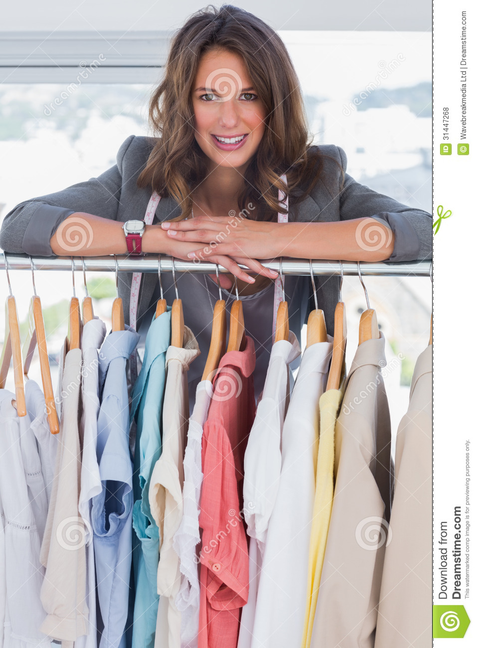 smiling fashion designer leaning on clothes stock photo