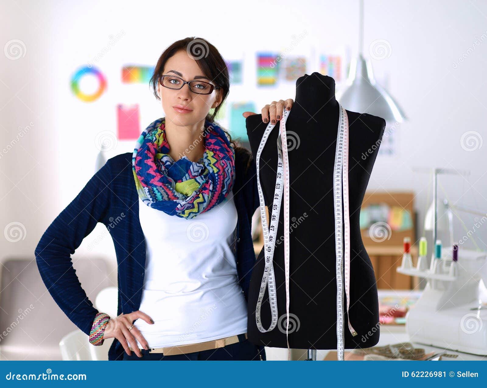 Smiling Fashion Designer Standing Near Mannequin Stock