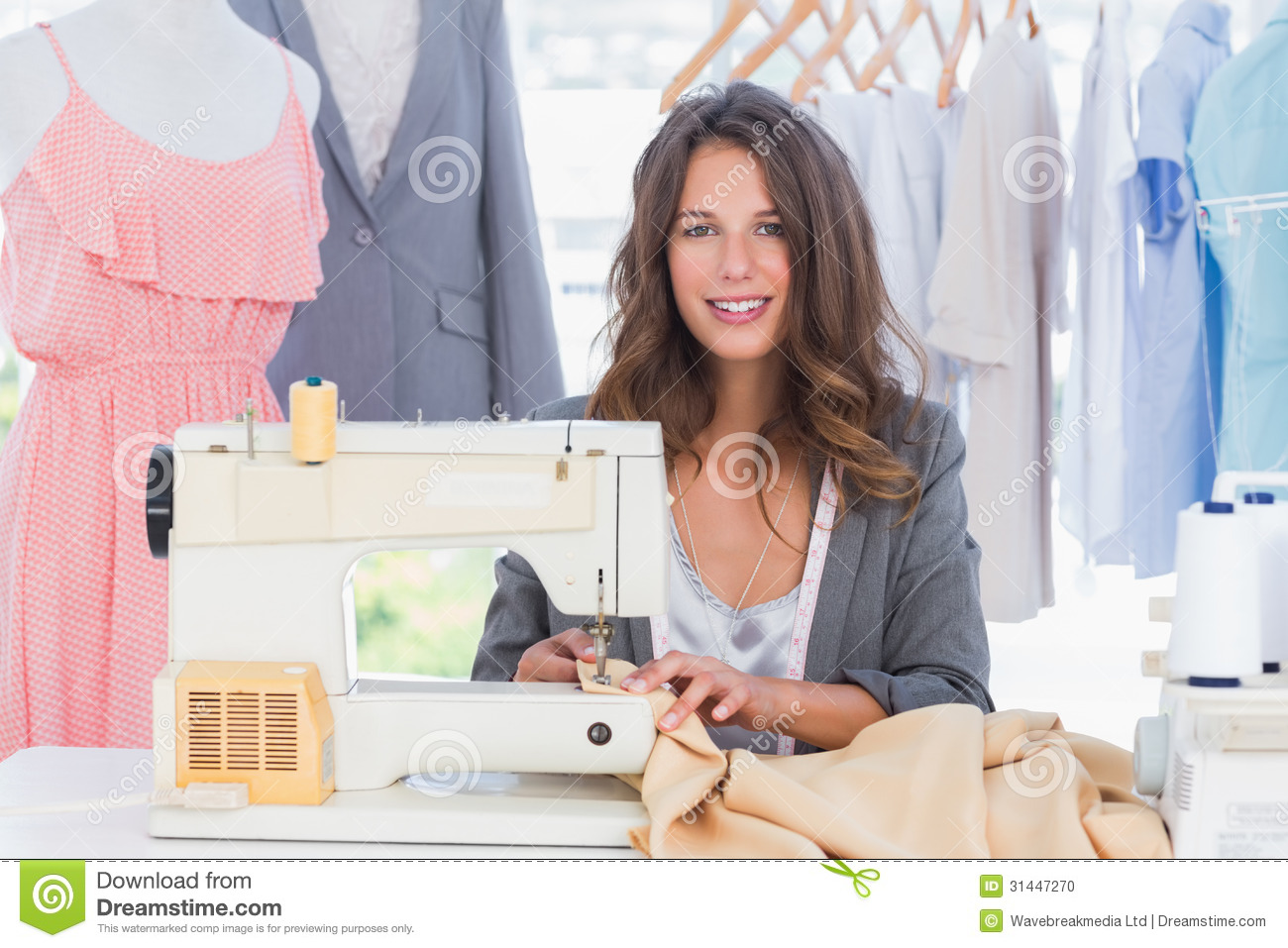 smiling fashion designer using sewing machine stock photo