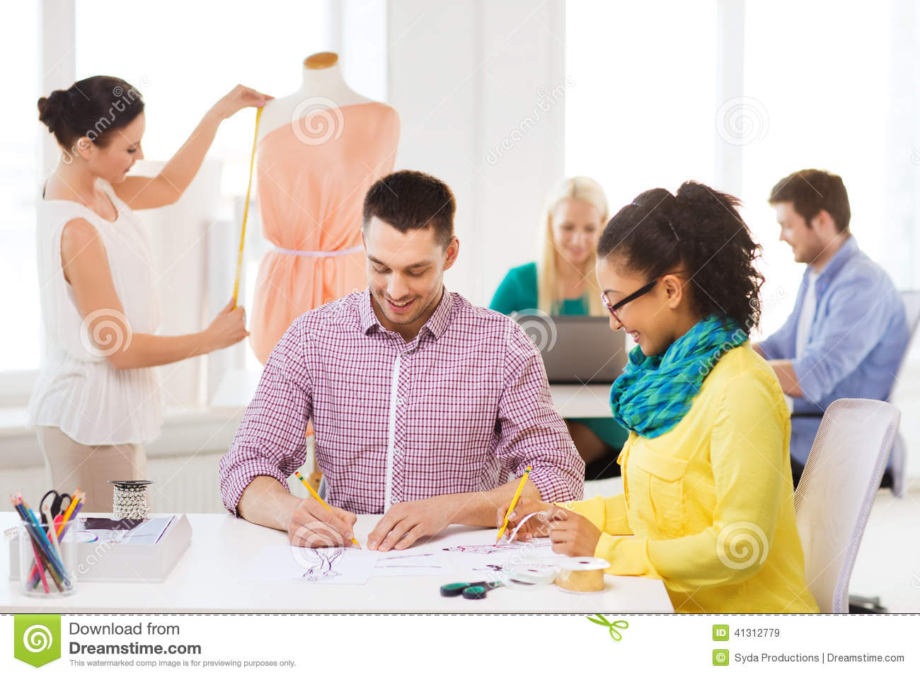 Smiling Fashion Designers Working In Office Stock