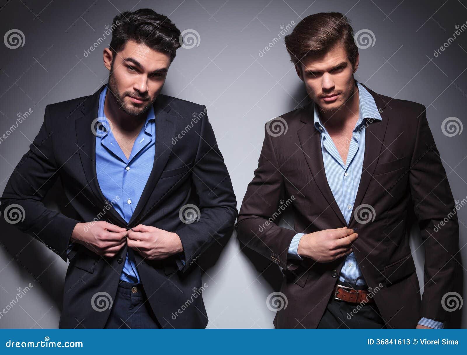 Smiling fashion men buttoning their coats