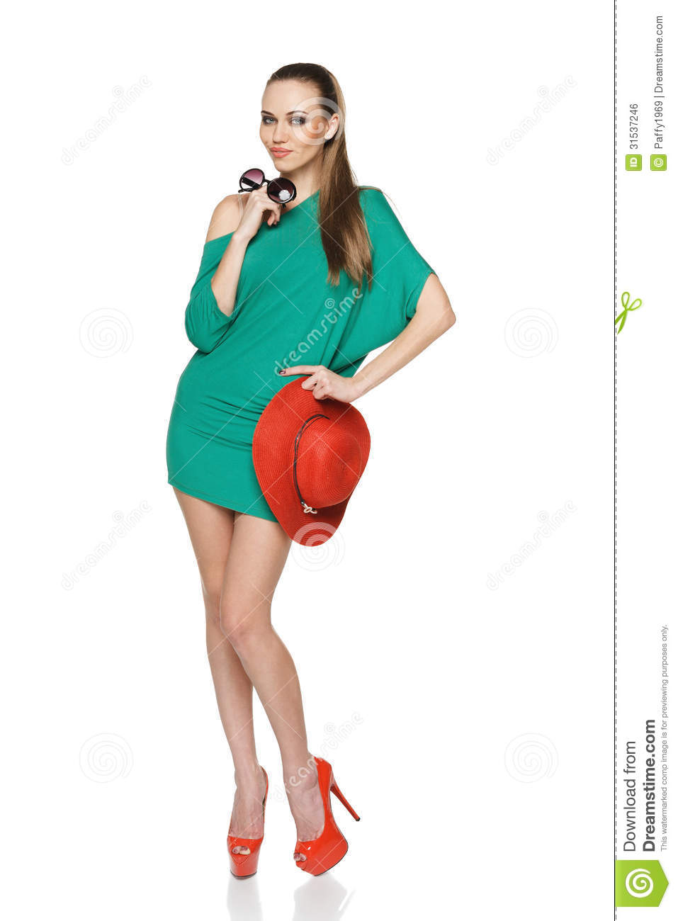 ... green dress and high heels red shoes holding straw hat and sunglasses