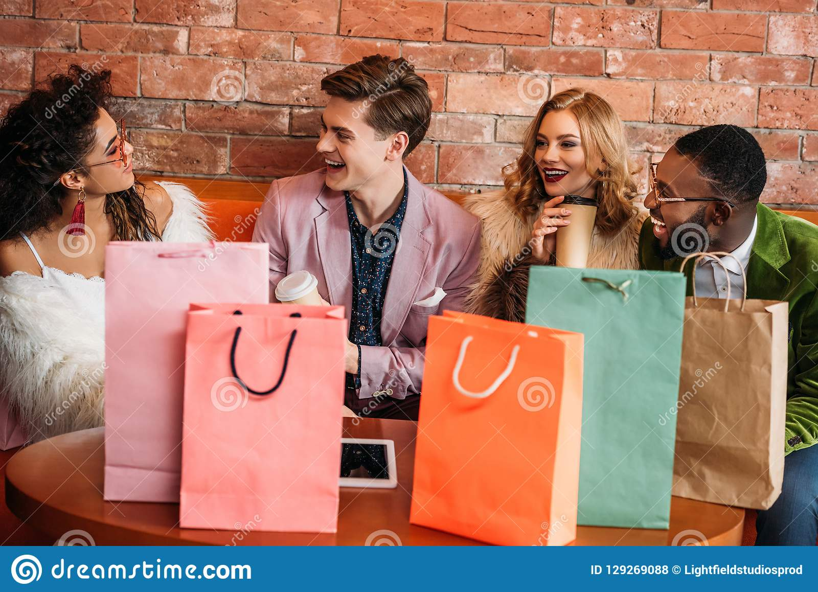 smiling fashionable multiethnic young people with shopping bags