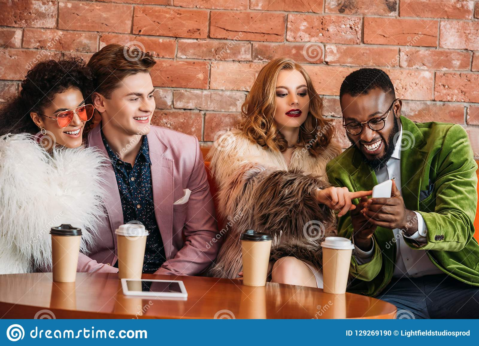 smiling fashionable multiethnic young people using smartphone while