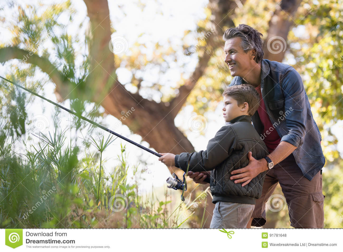 Smiling father assisting son while fishing in forest