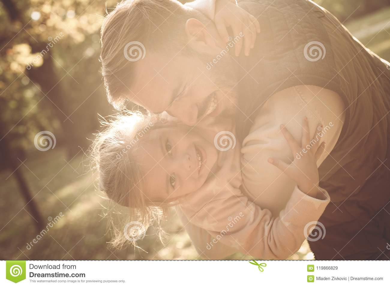 Smiling father and his little girl plying in park together.