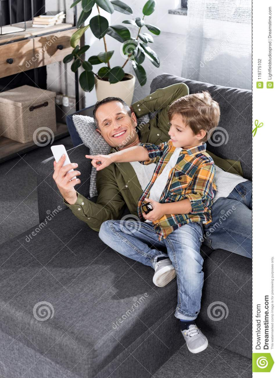 smiling father and little son using smartphone while resting on sofa