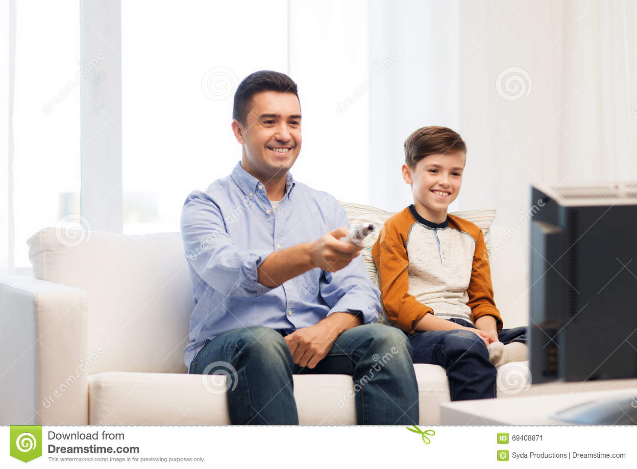 smiling father and son watching tv at home stock image image 69408871. Black Bedroom Furniture Sets. Home Design Ideas