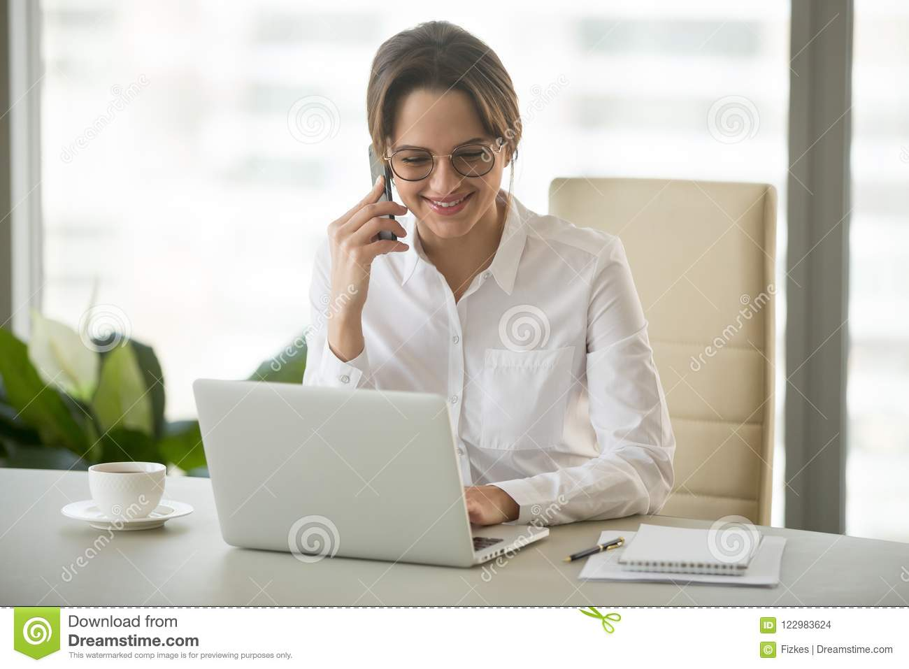 Smiling Businesswoman Talking On Phone While Working At
