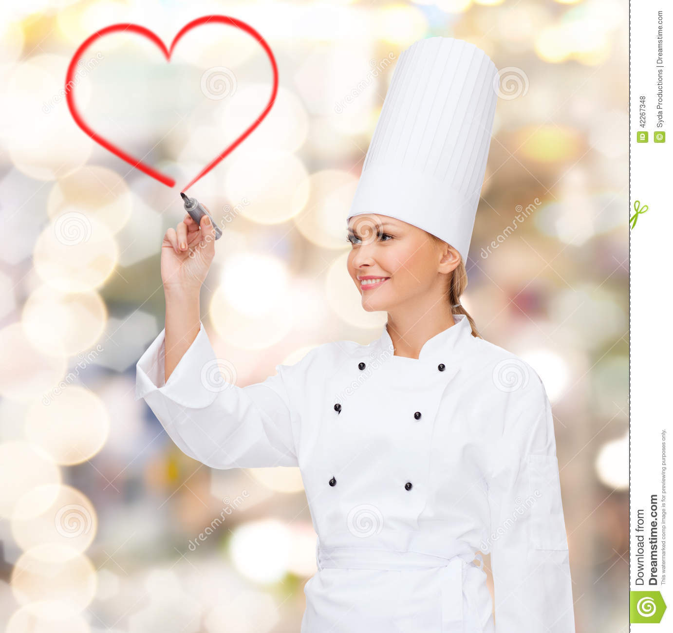 Smiling female chef drawing red heart on air