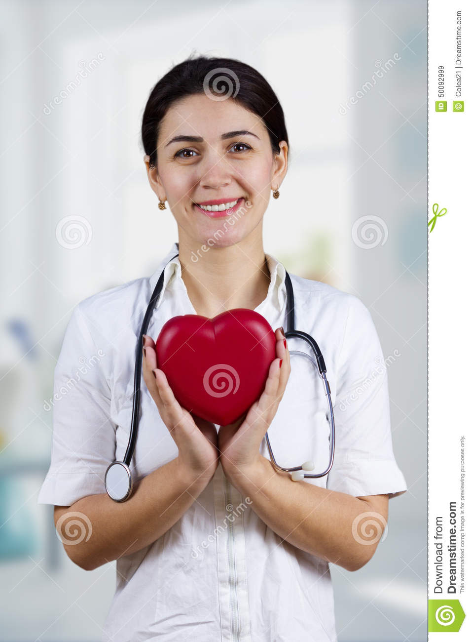 Smiling Female doctor holding red heart and stethascope