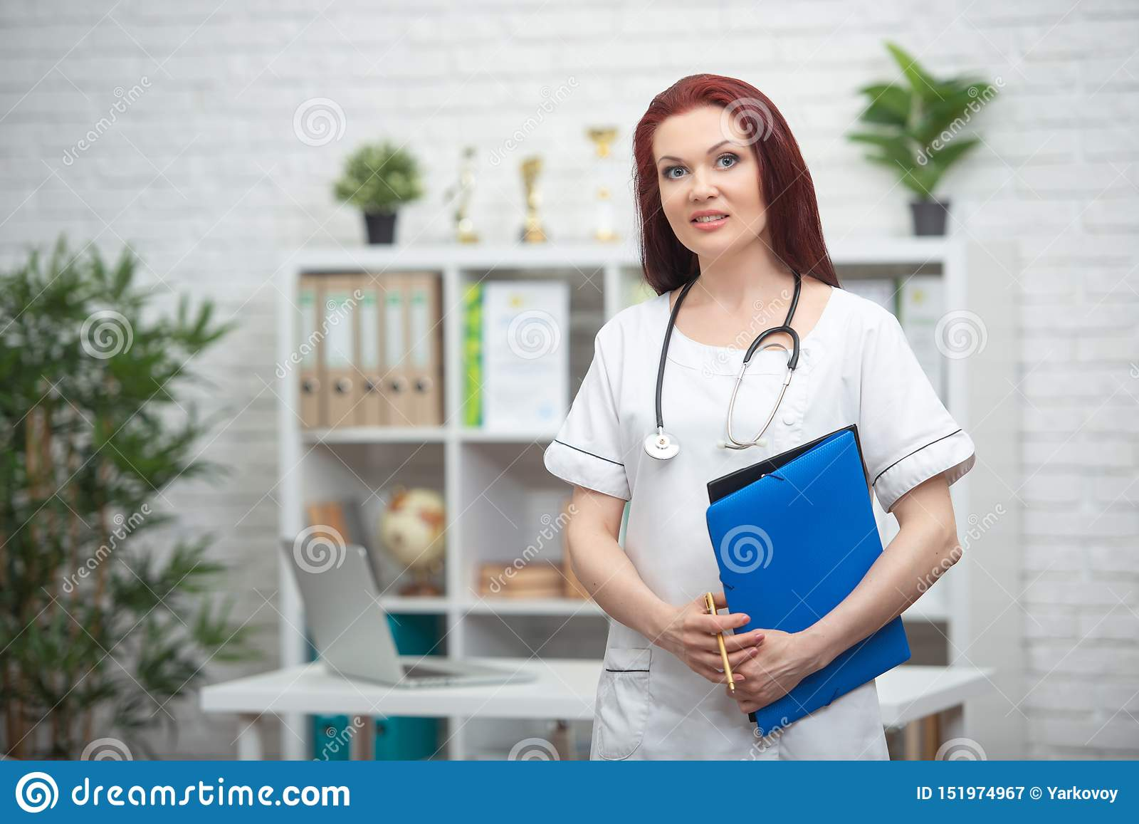 Smiling female doctor in uniform with a stethoscope and a blue folder in her hands is standing in his medical office and meets