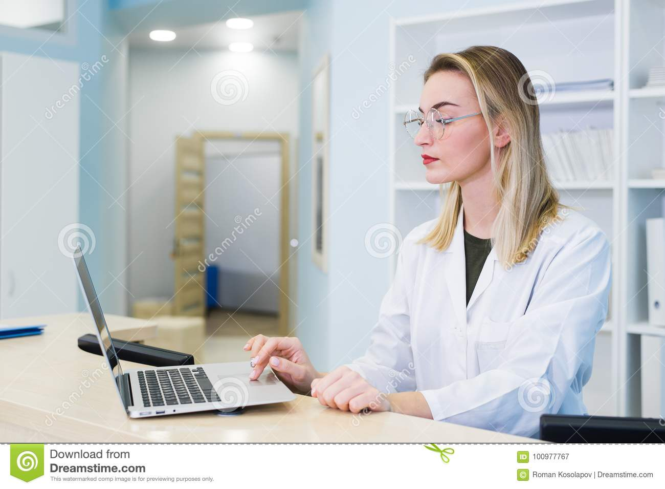 Smiling female doctor wearing a scrub and working at the hospital reception, she is writing a medical report on a