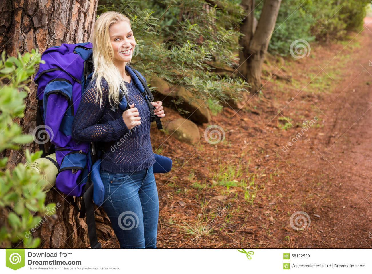 Smiling female hiker waiting by the side of the road