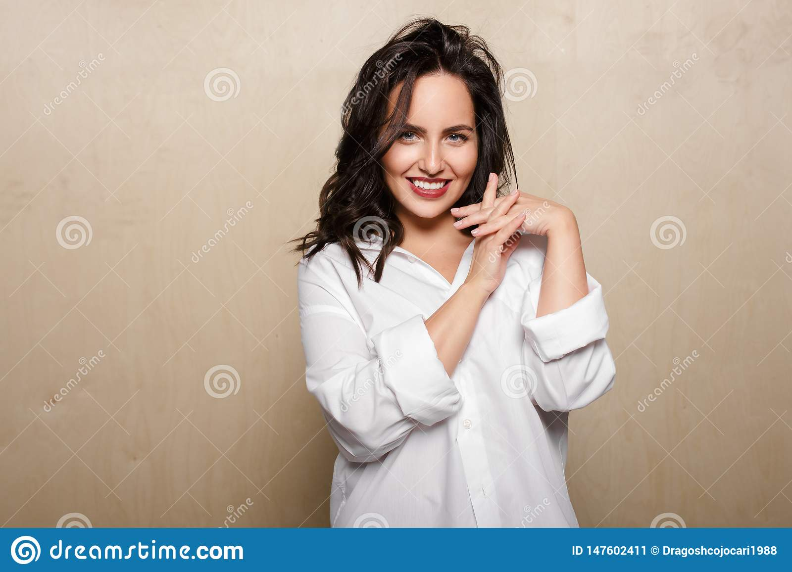Smiling female model in white shirt, on a beige background, holding a crossed fingers.