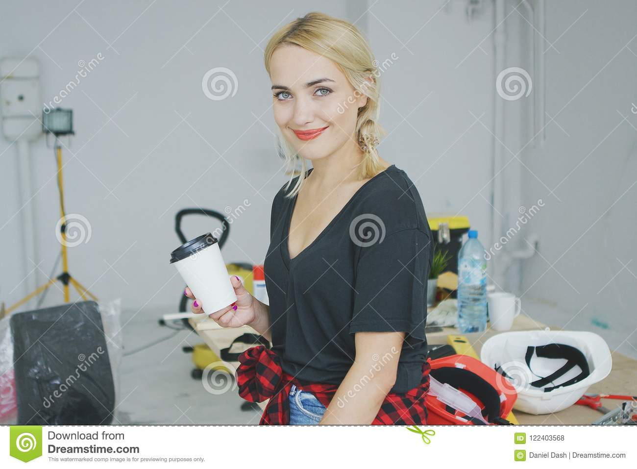 smiling female with paper cup in workshop stock photo