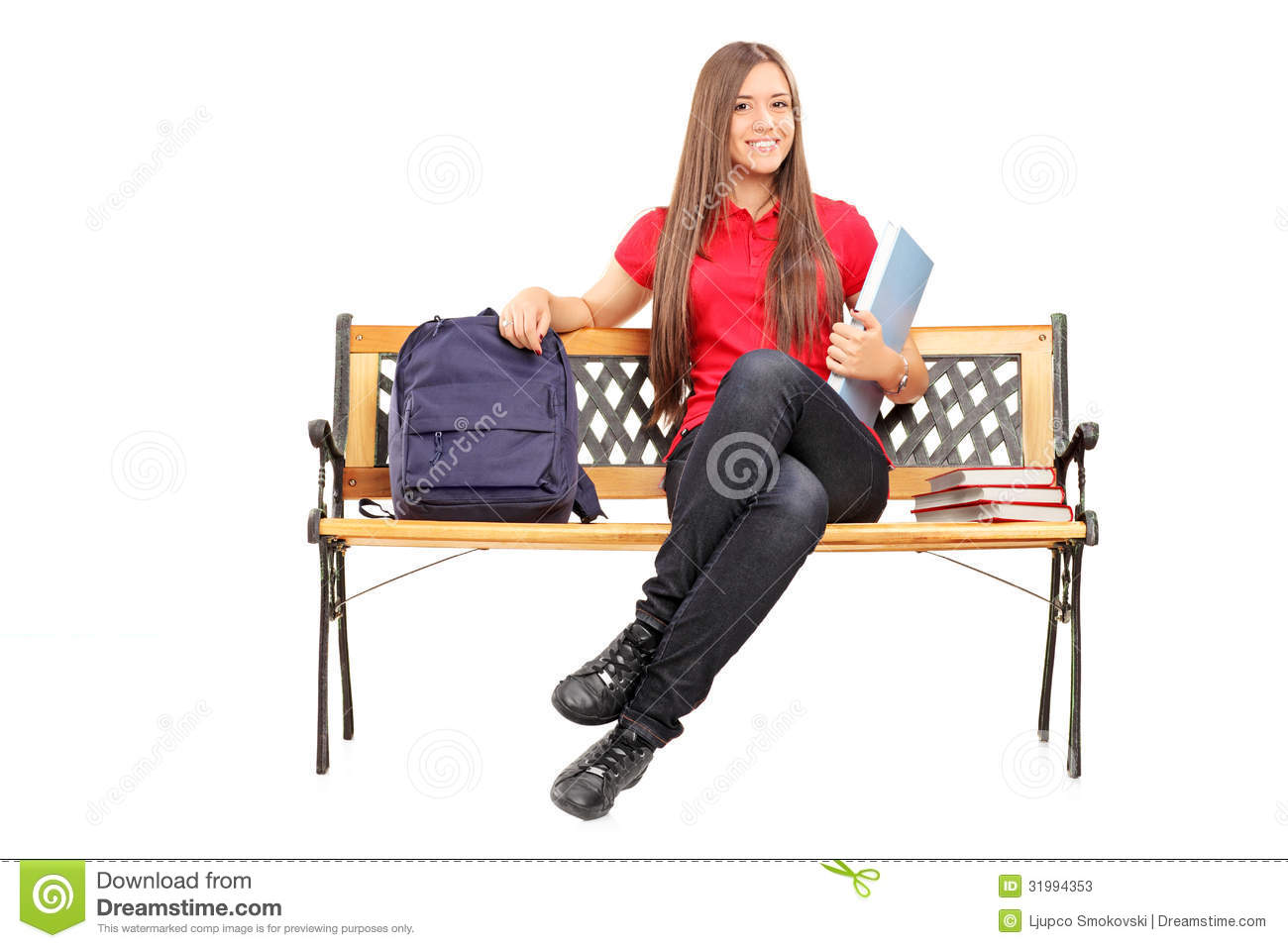 ... Photos: Smiling female student sitting on bench and holding a notebook