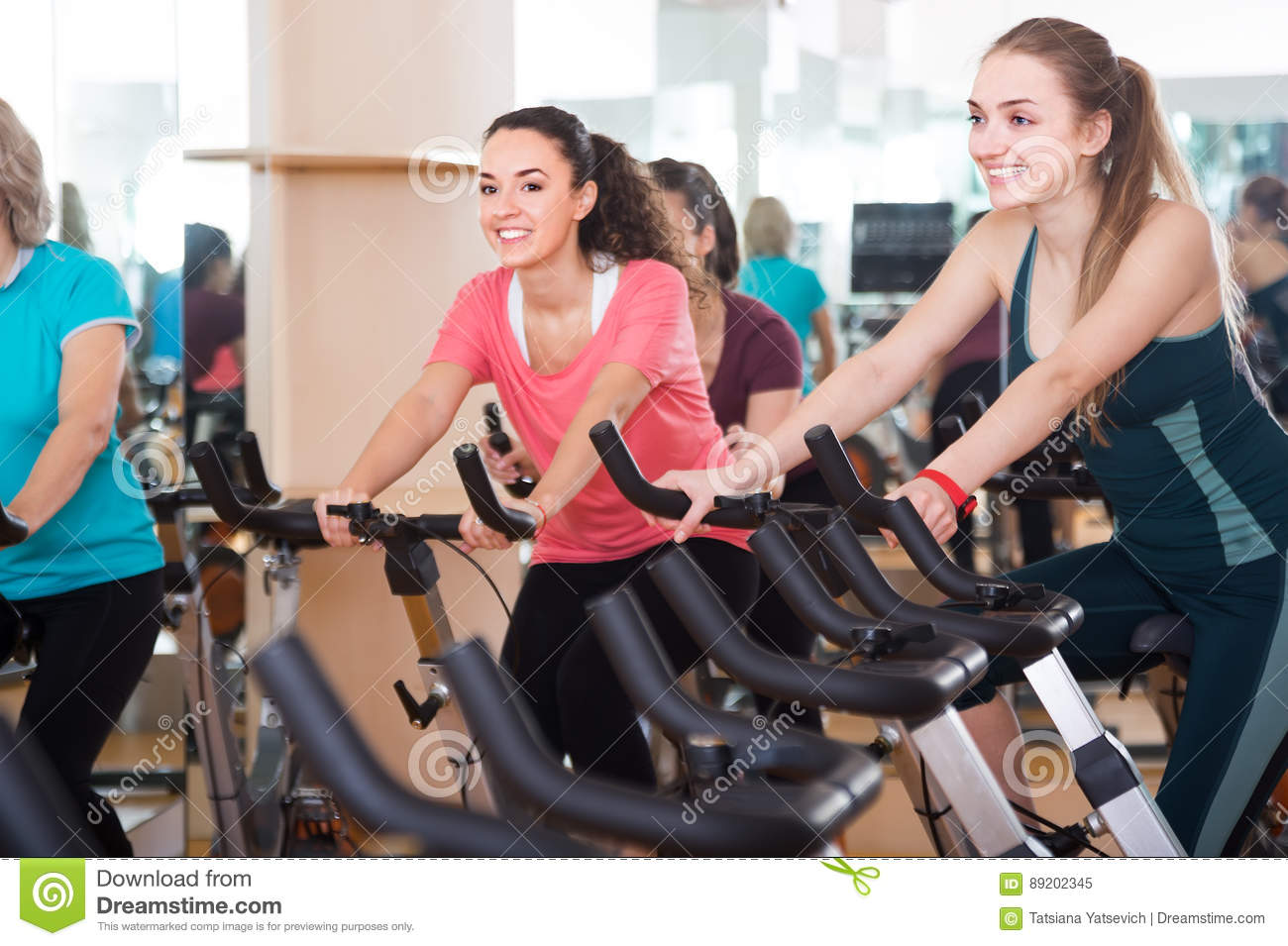 Smiling Females Of Different Age Training On Exercise Bikes Stock