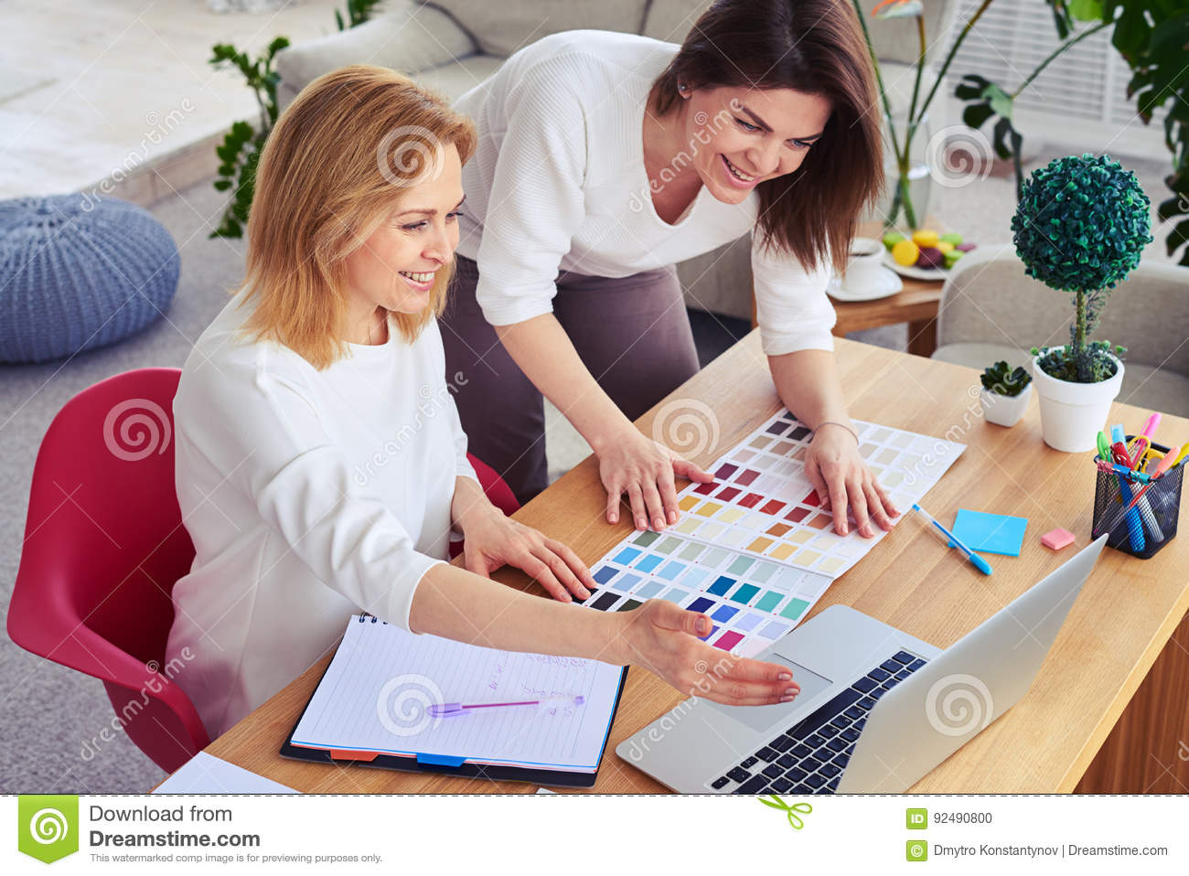 Smiling females working with catalog of color palette and laptop
