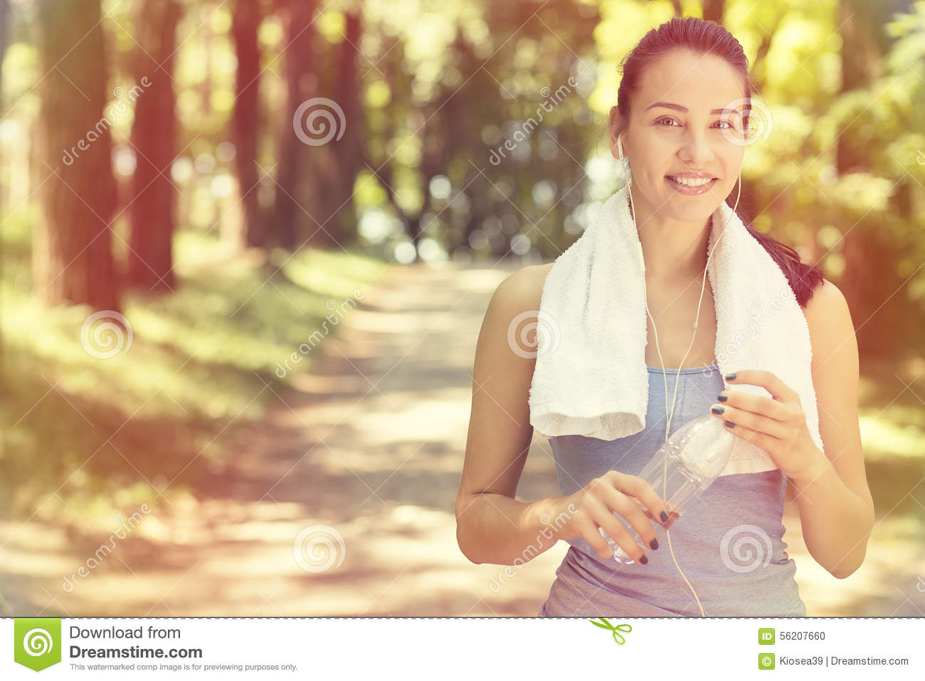 Smiling fit woman with white towel resting after sport exercises