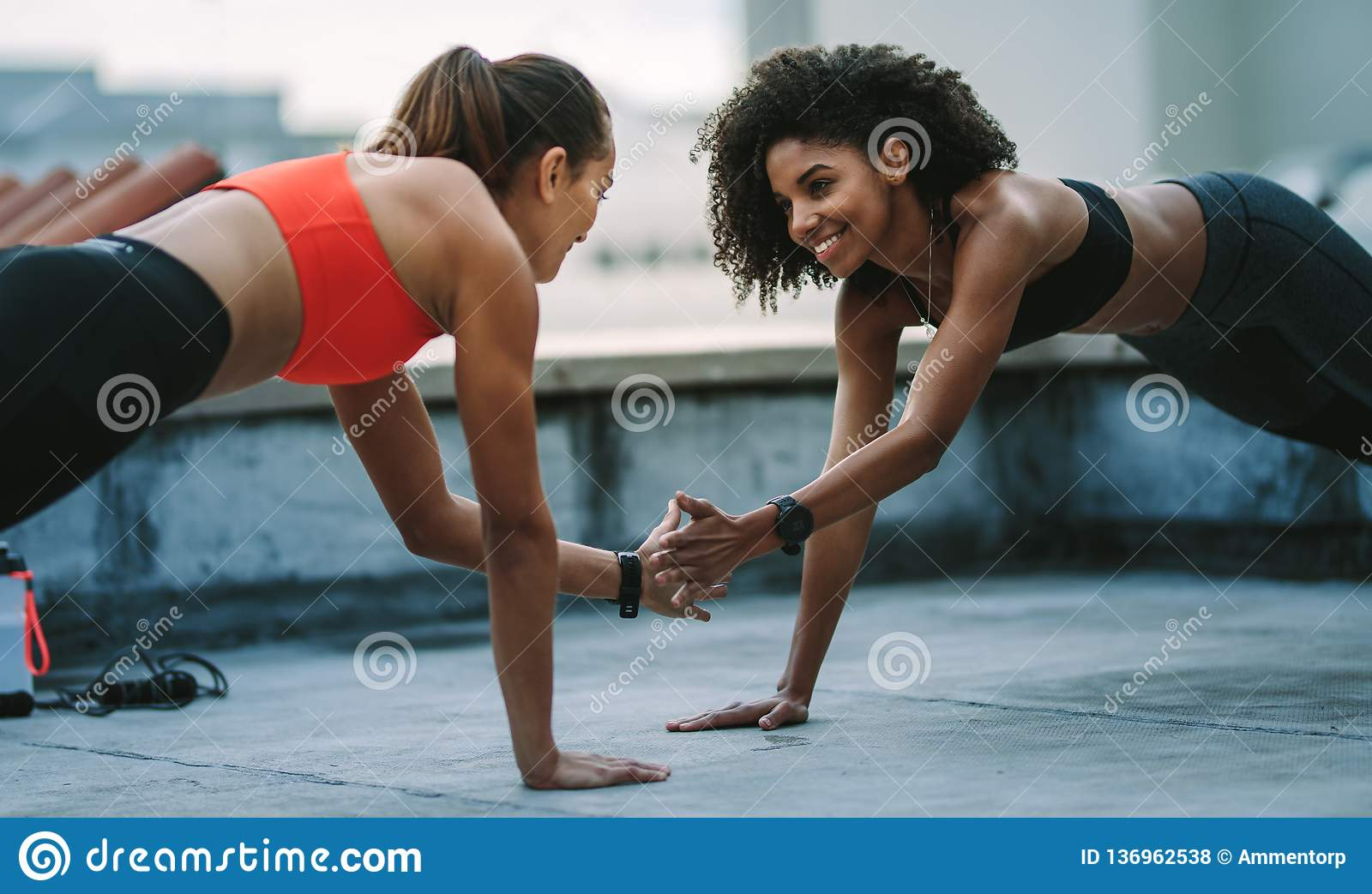 Two Fitness Women Training Together On Rooftop Stock Photo