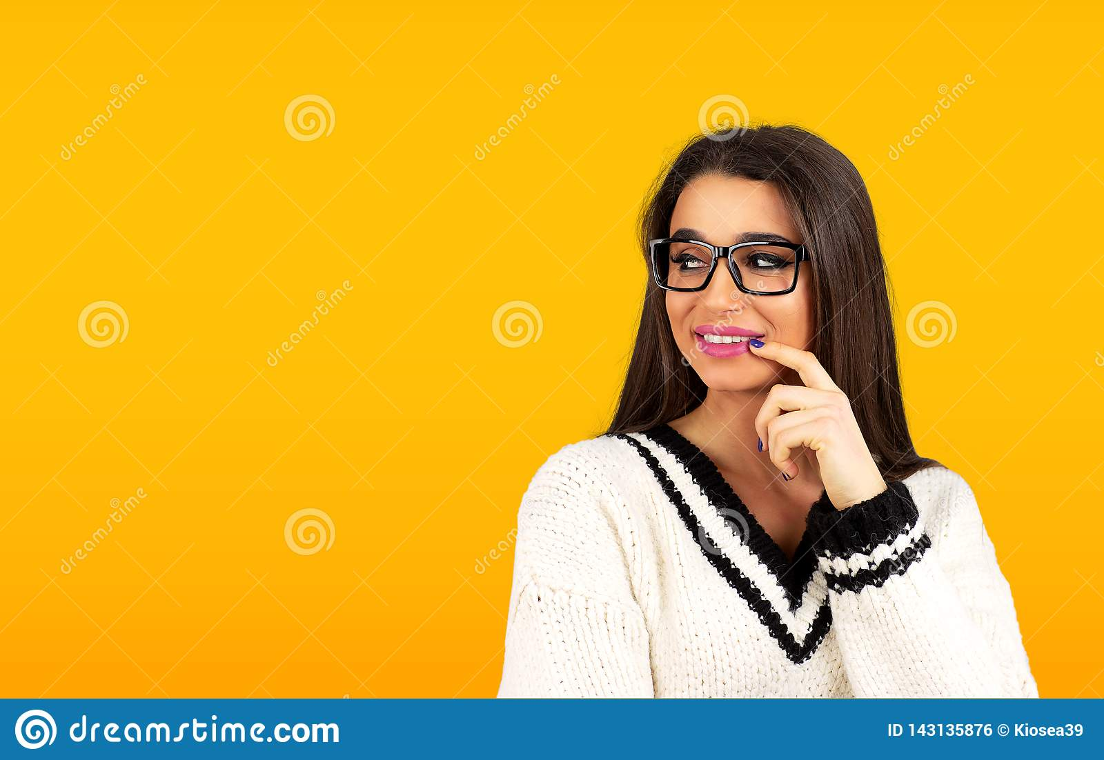 Smiling flirting woman with finger on lips looking sideways
