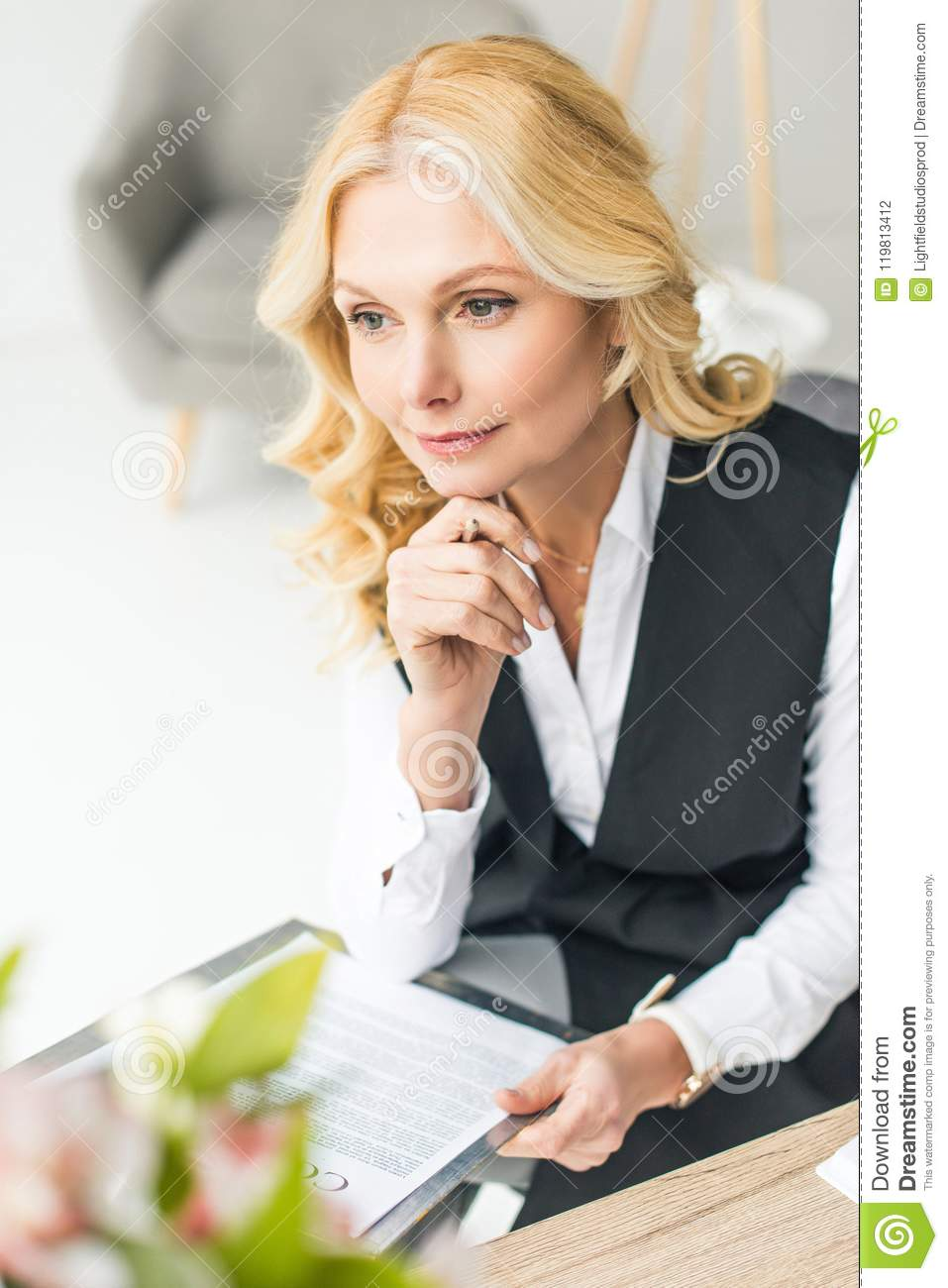 smiling focused businesswoman holding pen with contract and looking away